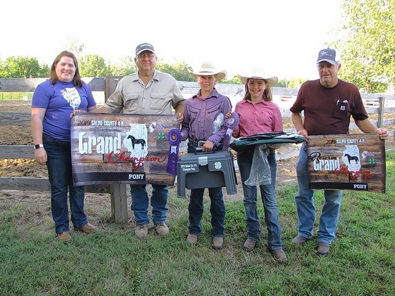 Grand Champion Pony, Shelby Pribble, and Reserve Champion Pony, Hannah Wenzel, are pictured with their ribbons, gifts and banners, and Saline County Farm Bureau Manager, Marisa Davis, and directors, Tom Wilson and Jim Patterson.